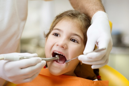 Little girl is having her teeth checked by dentist photo