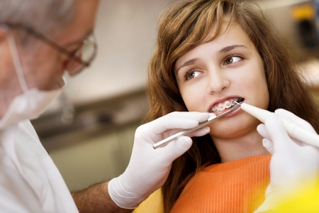 Teenage girl with the braces on her teeth is having a treatment at dentist Stock Photo - 17109634