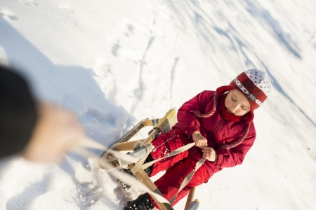 Little girl is playing outside in cold winter. photo