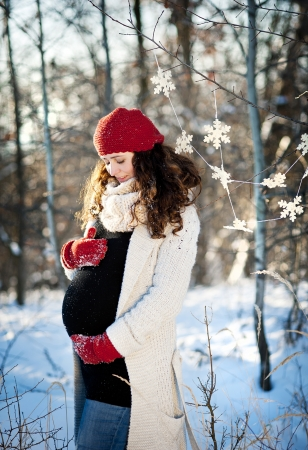 A beautiful outdoor pregnant woman portrait in snowy nature  photo