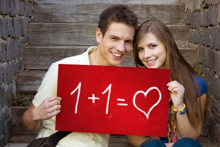 Young couple is holding board with romantic symbol. photo