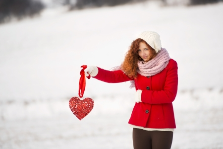 lonely girl: Lonely girl in the red coat is holding a red heart and waiting.