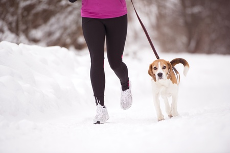 cold weather: Athlete woman is running during winter training outside in cold snow weather.
