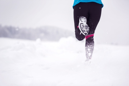 cold weather: Athlete woman is running during winter training outside in cold snow weather  Stock Photo