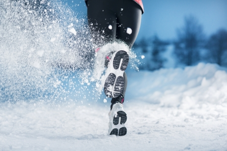 run woman: Athlete woman is running during winter training outside in cold snow weather  Stock Photo