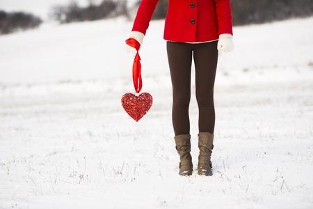 gente triste: Muchacha sola en la capa roja est� sosteniendo un coraz�n rojo y esperando Foto de archivo
