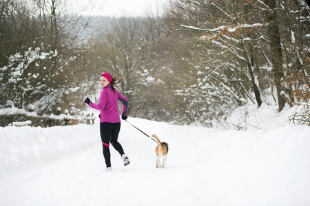Athlete woman is running during winter training outside in cold snow weather. photo
