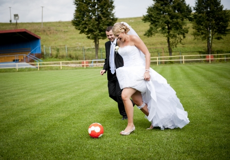 Bride and groom are playing at the football pitch photo