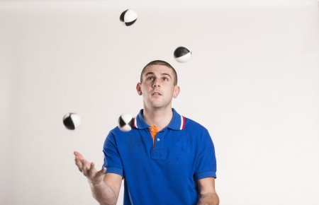 Young man juggling with several balls at once photo