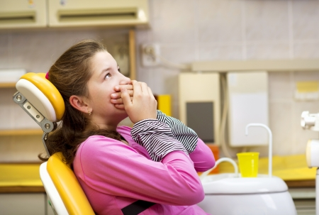 Little girl is being scared at the dentist photo