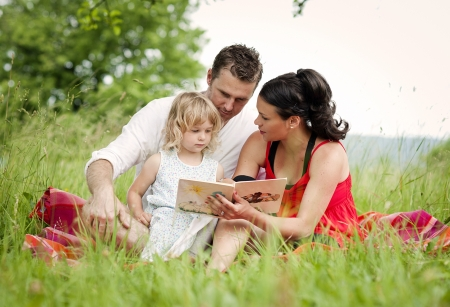 Happy family is playing together in a green meadow. photo