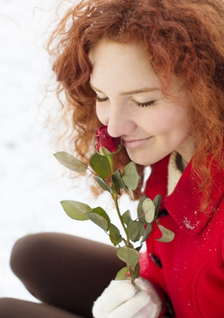Beautiful girl with roses in the snow in winter photo