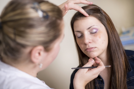Make up artist doing professional make up of young woman Stock Photo - 17850793
