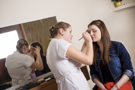 Make up artist doing professional make up of young woman photo