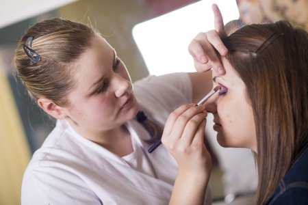 imperfection: Make up artist doing professional make up of young woman