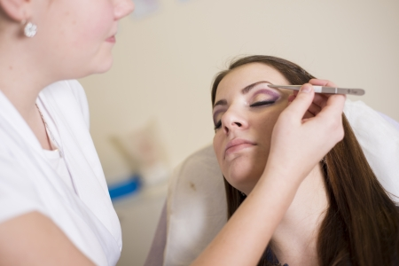 tweezing eyebrow: Make up artist doing professional make up of young woman