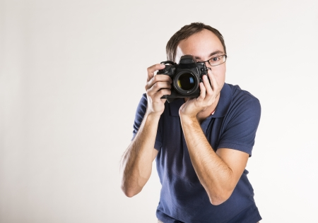 Young photographer with camera isolated on white background photo