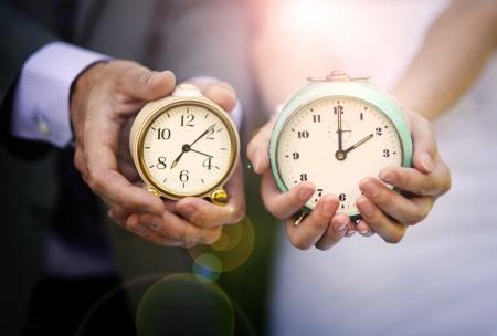 Wedding couple is holding clocks photo