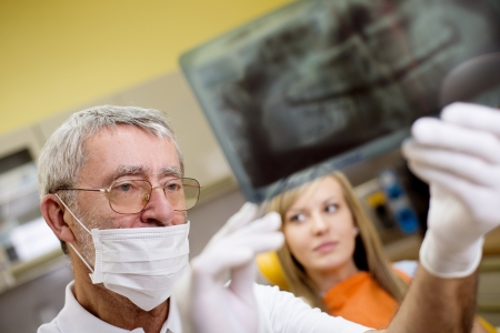 Dentist is showing the x ray of teeth to his patient  photo