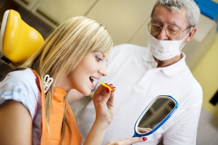 Dentist is showing the technique of teeth cleaning to his patient photo