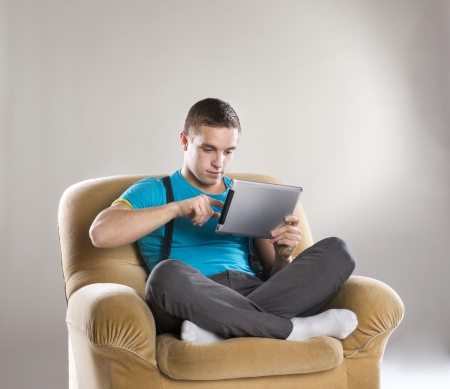 Handsome young man with tablet sitting in sofa photo