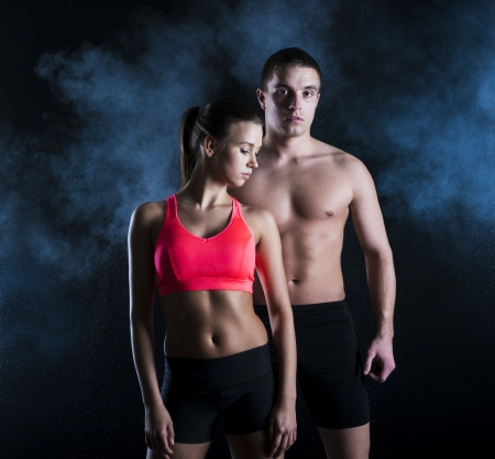 two couples: Young fitness models are posing in studio