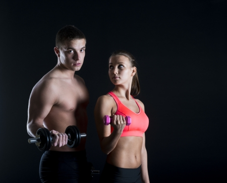 sexy couple black background: Young fitness models are posing in studio