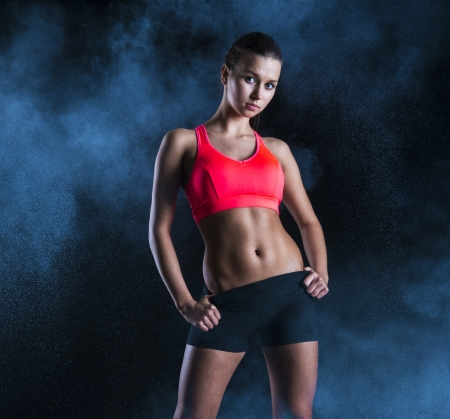 woman black background: Young fitness model is posing in studio