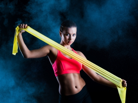 resistance: Young fitness model is posing in studio