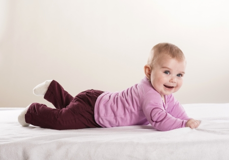 Sweet little baby is lying on mattress in studio photo