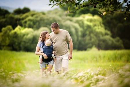 baby carrier: Family walking in the field with baby in the baby carrier Stock Photo