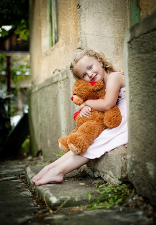 Little girl with her teddy is sitting in front of old door photo