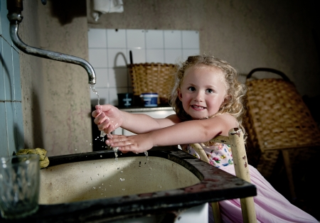 disinfecting: Little girl is washing her hands in old house Stock Photo