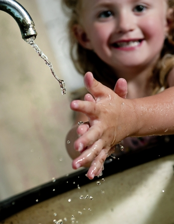 salud publica: La niña está lavando las manos en la vieja casa