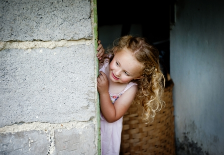 shy girl: Little girl is looking out of the door Stock Photo