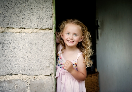 Little girl is looking out of the door photo