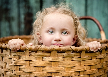 Little girl is playing outside and hiding in the wooden basket photo