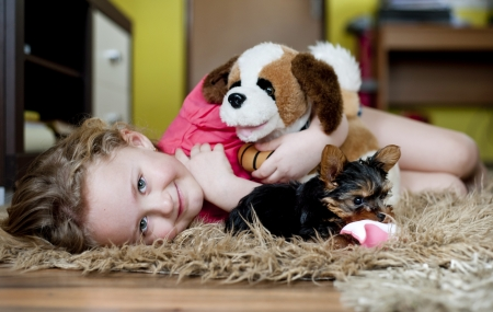 Little girl is playing with her puppy at home photo