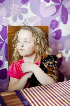 Little girl and her puppy are playing together in the kitchen photo