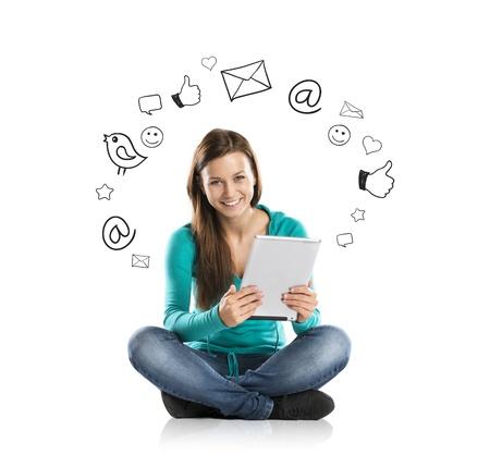 interaccion social: Chica joven hermosa con tableta está utilizando los medios sociales