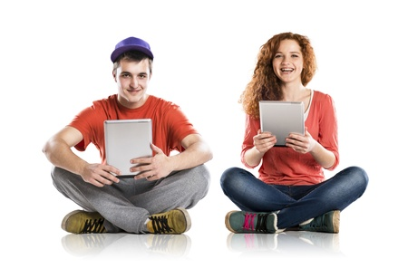 Beautiful young woman and man with tablet in studio photo