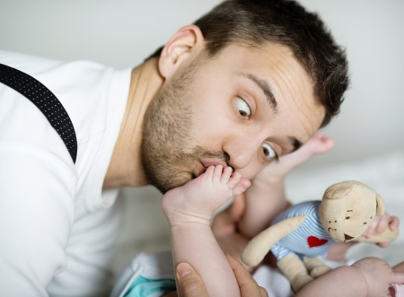 Young father is playing with his baby photo