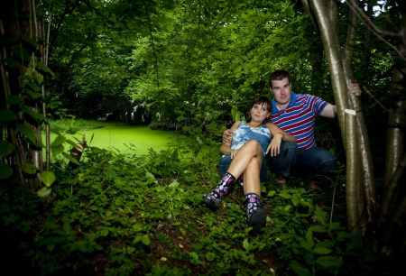 rest day: Happy pregnant couple is relaxing in nature Stock Photo