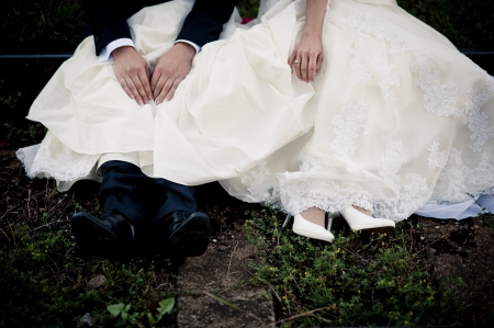 Bride and groom are sitting outside together photo