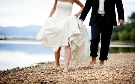 feet in sand: Bride and groom are walking outside together Stock Photo
