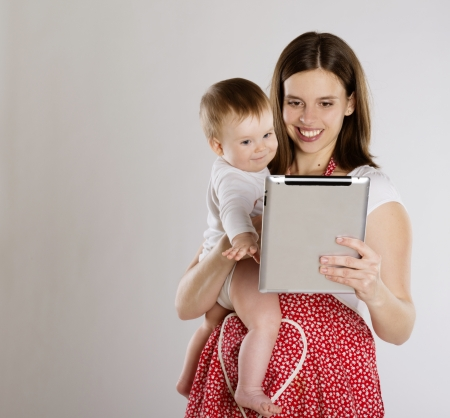 working mother: Young mother is looking at tablet with her baby Stock Photo