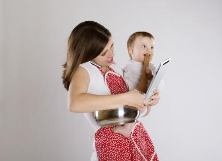 madre trabajando: Joven madre está mirando tablet con su bebé