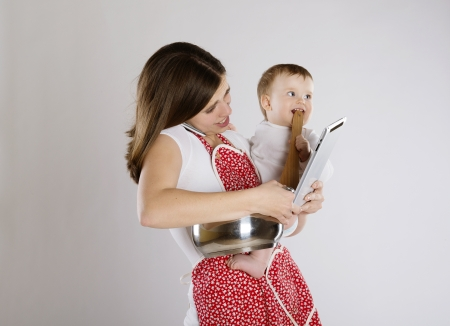 multitasking: Young mother is looking at tablet with her baby Stock Photo