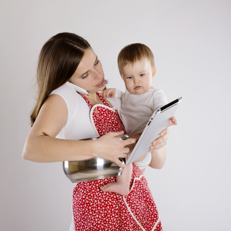 mum and baby: Young mother is looking at tablet with her baby Stock Photo