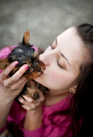 Young woman is outside with her yorkshire puppy photo